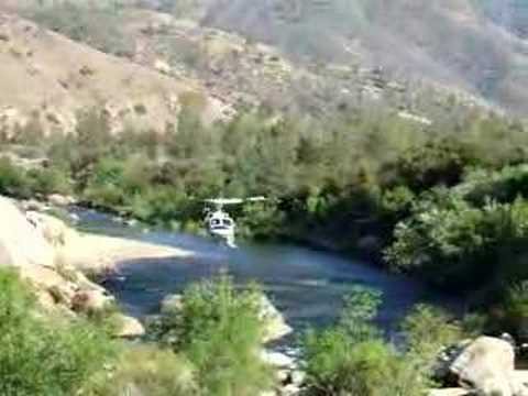 Firefighter helicopter loading H2O in Kern River, CA