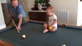 Baby playing pool can't stop laughing