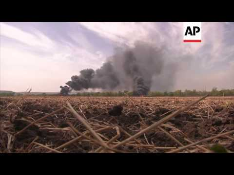 Unmarked military vehicles in flames in the road between Mariupol and Donetsk