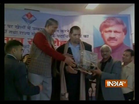 Uttarakhand CM Harish Rawat stands atop chair to felicitate wrestler Khali