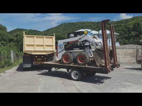 isuzu dump truck dropping off bobcat