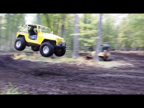Yellow Jeep Makes Big Jump Over Mud Hill