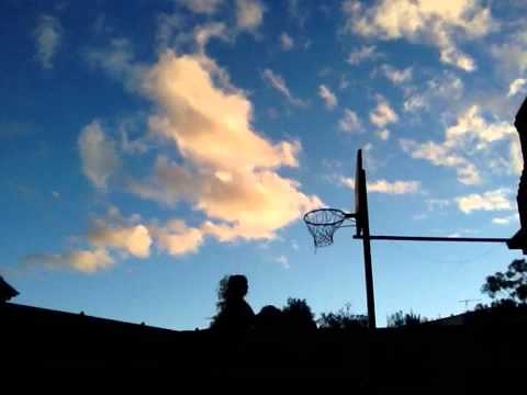 Slam dunking basketball on trampoline game