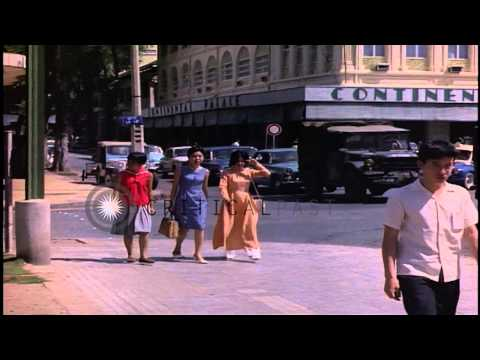 Vietnamese girls walk along a sidewalk and vehicular traffic on a road in Saigon,...HD Stock Footage
