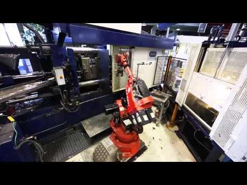Comau NM 45 in aluminum die casting machine tending