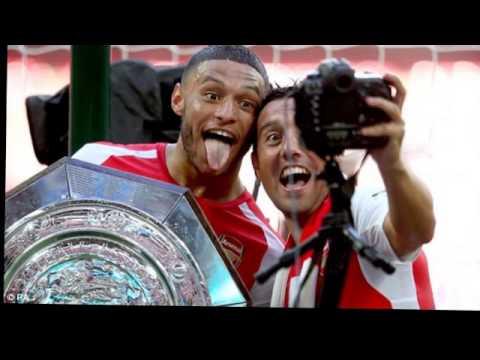 Theo Walcott and Wojciech Szczesny pose with Arsenal trophies..