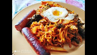 Eating very spicy noodles with sausage , french fries and egg