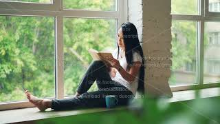 Attractive Asian girl student is reading book and smiling sitting on window ledge in modern