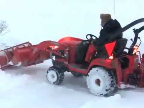Kubota BX clearing snow with BXpanded plow and bucket