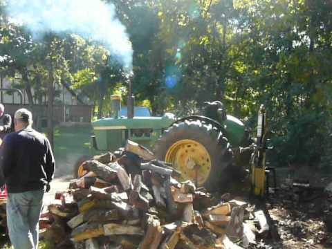 John Deere 4010 Diesel being used to split logs and Kubota with loader moving th