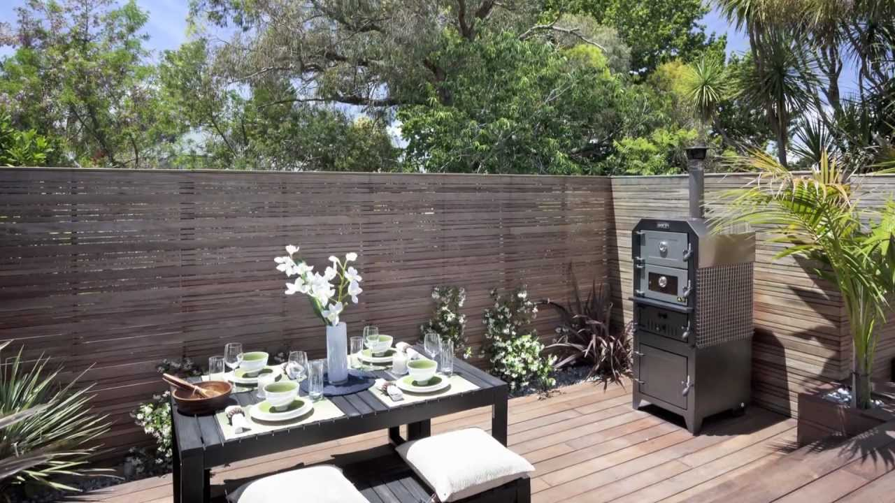 Hardwood deck built over sloping land provides outdoor for Small backyard entertaining ideas