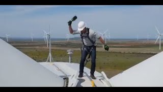 Jeff Bezos smashes bottle of champagne while perched on top of a giant wind mill