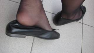 black Tamaris leather ballet flats and black nylons , balcony shoeplay and dangling