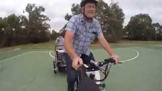 Electric bike, baby trailer and kid on skateboard