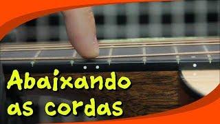 Abaixando as cordas de um violão folk