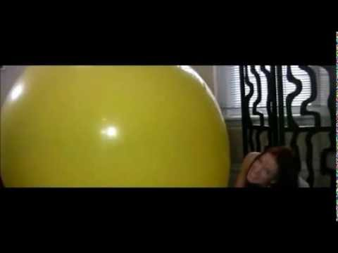 Girl  inflates a huge yellow balloon.