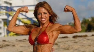 Jeannette Jarnes Figure Model posing in a Hot Red Bikini while doing Muscles Flexing on the beach