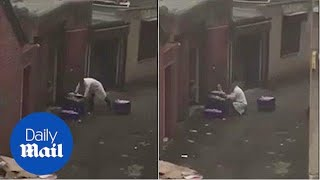 Shocking moment butcher seems to cut chicken in dirty street - Daily Mail