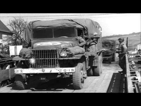 Military trucks cross the first American Bailey bridge across the Rhine River in
