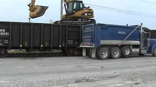 Cat 319DL unloading rock from a train