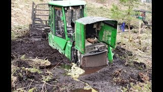 John Deere 1110E stuck in mud, saving with a powerful winch mounted on homemade forwarder