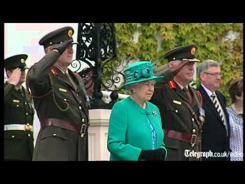 The Queen stood side by side with Prime Minister Enda Kenny as the Irish military band played the British and Irish national anthems. She then signed the vis...