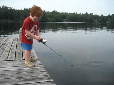 Four-year-old boy dances and then catches a sunfish on a lake in New Hampshire using bread as bait.