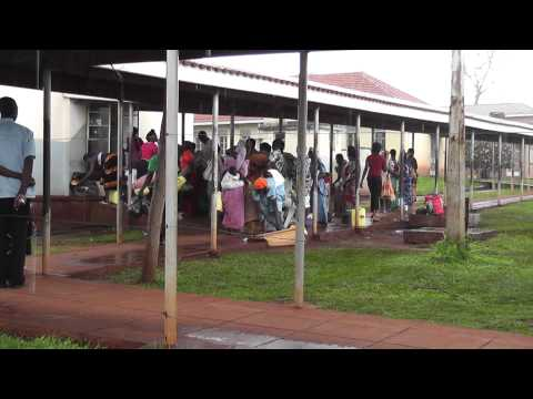Women wait outside in the rain for treatment at hospital in Jinja, Uganda