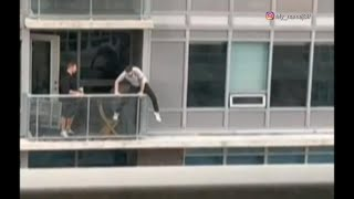 Man goes out on building's exterior ledge to retrieve cat