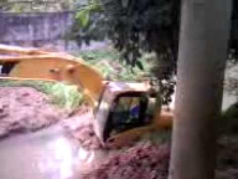 escavadeira atolada em corrego