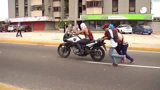 Policía pistola en mano en protesta  recupera Moto secuestrada por manifestantes en Venezuela