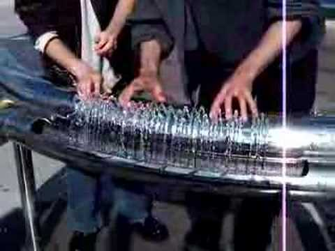 Two people playing hydraulophone (water pipe organ flute)
