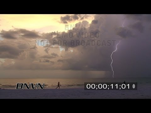 8/28/2007 Joggers on a beach with Lightning strikes off shore