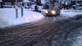 Big quad and volvo 340 drifting in snow around the round about.