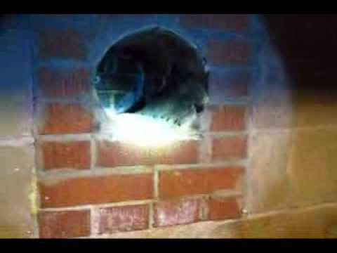 Installing a stove pipe through wall in an existing masonry chimney DIY Do it yourself how to video.