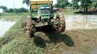 John Deere 5055e four wheel drive tractor stuck in mud puddling time rice framing