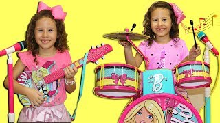 Valentina plays with a toy battery and Disney guitar  and starts a band complete