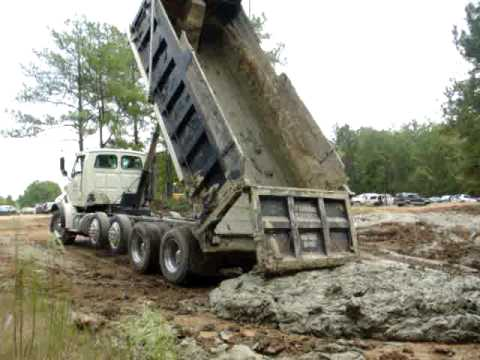 Dump trucks dumping mud Video