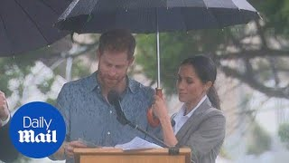 Meghan holds an umbrella for Harry as he speaks in Dubbo