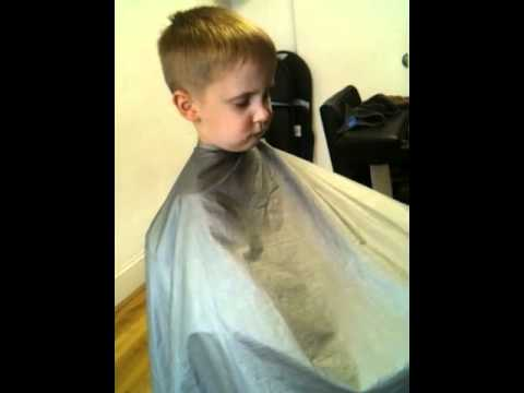 Cute little boy falls asleep getting his hair cut.