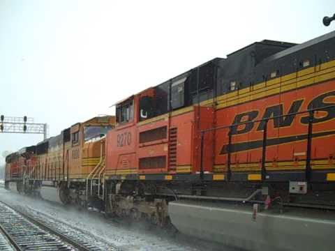 BNSF ES44AC GEVO #6087, SD70MAC #8800 (the lowest-numbered '70MAC on BNSF's roster), and SD70ACe #9270 power a fast manifest freight through powdery, freshly...