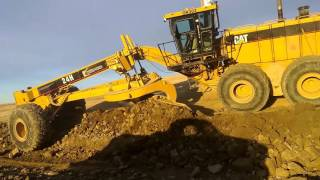 CAT 24 Grader Trimming Rock Slope