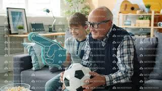 Joyful family grandfather and grandson watching football on TV cheering hugging