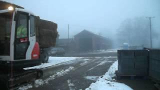Mini excavator clearing snow.