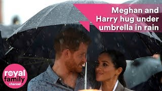 Prince Harry and Meghan hug under umbrella as they bring English weather to drought-stricken Dubbo