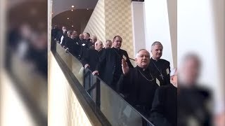 Nine minutes of Bishops coming down escalator  in high speed
