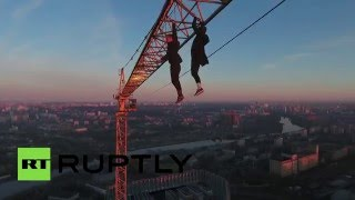 Fearless daredevils hang over Moscow with one arm