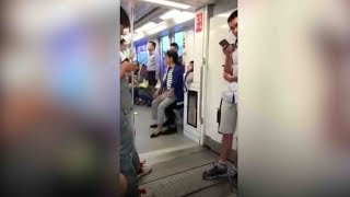 Elderly woman sits on man's lap on the subway after man refuses to give up seat