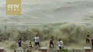 فيديو: موجة مد تفاجىء المارة على ضفة نهر فى الصين