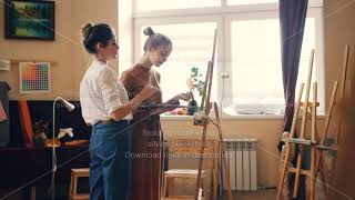 Attractive girl student is painting during art class in studio, her teacher is coming and helping